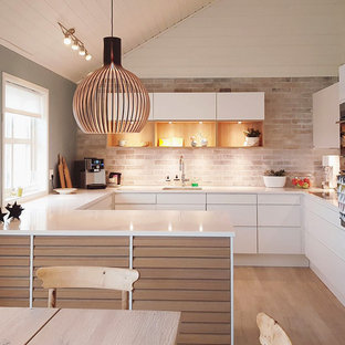 Inspiration for a scandinavian u-shaped eat-in kitchen in Aarhus with an undermount sink, flat-panel cabinets, white cabinets, beige splashback, brick splashback, panelled appliances, medium hardwood floors, a peninsula, beige floor and white benchtop.