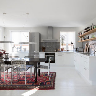 Design ideas for a mid-sized contemporary l-shaped eat-in kitchen in Copenhagen with an integrated sink, flat-panel cabinets, white cabinets, laminate benchtops, grey splashback, porcelain splashback, black appliances, painted wood floors and no island.
