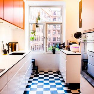 Zweizeilige, Kleine Moderne Küche ohne Insel mit flächenbündigen Schrankfronten, orangefarbenen Schränken, Einbauwaschbecken, Laminat-Arbeitsplatte, Küchengeräten aus Edelstahl und Linoleum in Aalborg
