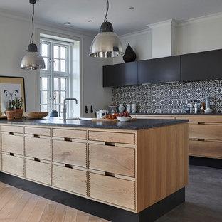 Foto di una cucina scandinava con ante lisce, ante nere, paraspruzzi multicolore, pavimento in cemento e penisola