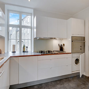 Mid-sized scandinavian enclosed kitchen pictures - Example of a mid-sized danish l-shaped ceramic floor enclosed kitchen design in Aalborg with a drop-in sink, flat-panel cabinets, white cabinets, stainless steel appliances, no island, laminate countertops, gray backsplash and glass sheet backsplash