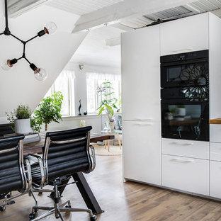 コペンハーゲンの中サイズのエクレクティックスタイルのおしゃれなLDK (シングルシンク、フラットパネル扉のキャビネット、白いキャビネット、木材カウンター、大理石のキッチンパネル、黒い調理設備、ラミネートの床) の写真