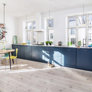 Inspiration for a scandinavian single-wall eat-in kitchen in Copenhagen with an integrated sink, flat-panel cabinets, blue cabinets, stainless steel benchtops, panelled appliances, light hardwood floors, no island and beige floor.