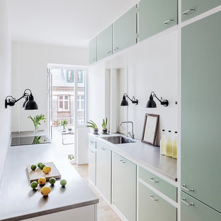 Inspiration for a scandinavian galley separate kitchen in Copenhagen with an integrated sink, flat-panel cabinets, green cabinets, concrete benchtops, grey splashback, light hardwood floors, no island and beige floor.