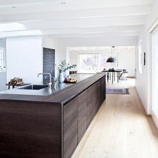Esempio di una grande cucina abitabile minimalista con lavello integrato, ante lisce, ante in legno bruno, top in legno, parquet chiaro e isola