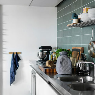 Inspiration for a scandinavian kitchen in Aarhus with a double-bowl sink, flat-panel cabinets, white cabinets, stainless steel benchtops, green splashback, stainless steel appliances, green floor and grey benchtop.