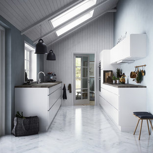 Inspiration for a large scandinavian galley separate kitchen in Copenhagen with a drop-in sink, louvered cabinets, white cabinets, wood benchtops, black appliances, marble floors and no island.