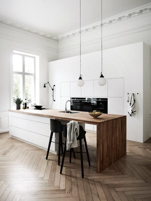 Zweizeilige Skandinavische Küche Mit Unterbauwaschbecken, Flächenbündigen  Schrankfronten, Weißen Schränken, Arbeitsplatte Aus Holz,