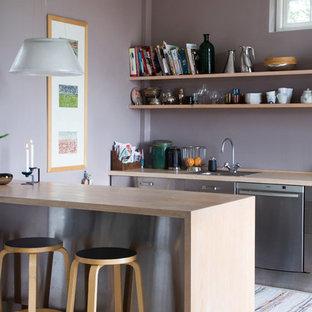 Bild på ett avskilt, mellanstort minimalistiskt parallellkök, med en nedsänkt diskho, släta luckor, skåp i rostfritt stål, rostfria vitvaror, ljust trägolv, en halv köksö och träbänkskiva