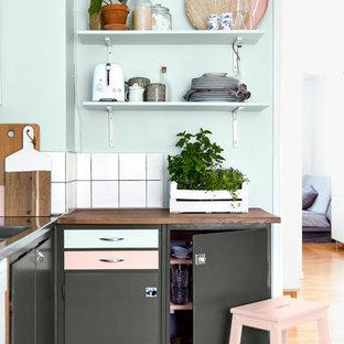 Foto på ett minimalistiskt l-kök, med en nedsänkt diskho, släta luckor, grå skåp, träbänkskiva, vitt stänkskydd och ljust trägolv