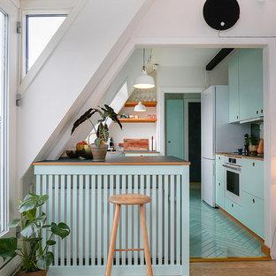 Aménagement d'une petit cuisine scandinave avec un placard à porte plane, des portes de placard turquoises, un plan de travail en bois, une péninsule et un sol turquoise.