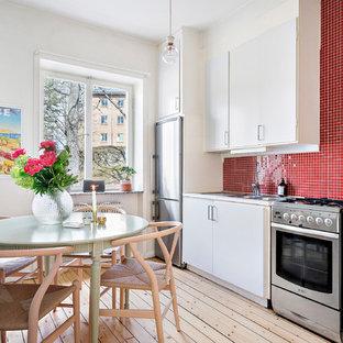 Scandinavian kitchen designs - Inspiration for a scandinavian single-wall kitchen remodel in Copenhagen with wood countertops and red backsplash