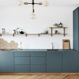 Inspiration for a large scandinavian l-shaped eat-in kitchen in Copenhagen with a single-bowl sink, flat-panel cabinets, blue cabinets, brown splashback, timber splashback, coloured appliances, medium hardwood floors, with island and brown floor.