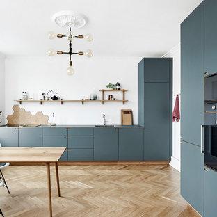 Idéer för ett stort nordiskt kök, med släta luckor, blå skåp, en enkel diskho, brunt stänkskydd, stänkskydd i trä, färgglada vitvaror, ljust trägolv och beiget golv