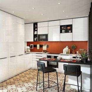 他の地域のコンテンポラリースタイルのおしゃれなキッチン (フラットパネル扉のキャビネット、白いキャビネット、オレンジのキッチンパネル、マルチカラーの床、白いキッチンカウンター) の写真