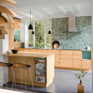 Inredning av ett nordiskt mellanstort kök, med släta luckor, skåp i ljust trä, grönt stänkskydd, en halv köksö, en nedsänkt diskho, träbänkskiva och linoleumgolv