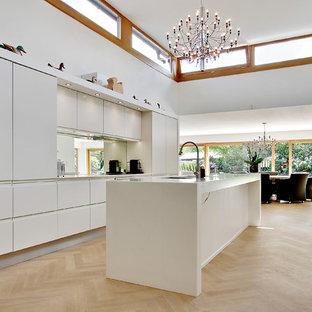 Diseño de cocina de galera, minimalista, grande, abierta, con fregadero de un seno, armarios con paneles lisos, puertas de armario blancas, encimera de laminado, electrodomésticos de colores, suelo de madera clara y una isla