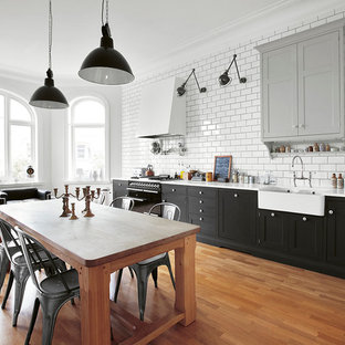 Photo of a large industrial single-wall eat-in kitchen in Copenhagen with an undermount sink, recessed-panel cabinets, black cabinets, recycled glass benchtops, black appliances, medium hardwood floors and no island.
