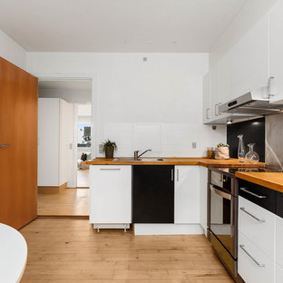 This is an example of a midcentury l-shaped eat-in kitchen in Copenhagen with flat-panel cabinets, wood benchtops, metallic splashback, stainless steel appliances and orange benchtop.