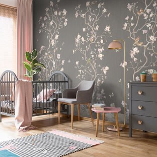 Ejemplo de habitación de bebé niña actual, grande, con paredes grises, suelo de madera clara y suelo beige