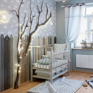 This is an example of a traditional gender neutral nursery in Other with multi-coloured walls, light hardwood flooring and beige floors.