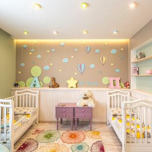 На фото: маленькая комната для малыша в стиле современная классика с полом из ламината, бежевым полом и разноцветными стенами для девочки с