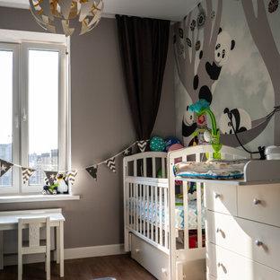 Immagine di una cameretta per neonato minimal di medie dimensioni con pareti grigie, pavimento in legno massello medio, pavimento marrone e carta da parati