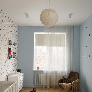 На фото: нейтральная комната для малыша в современном стиле с синими стенами, светлым паркетным полом и коричневым полом с