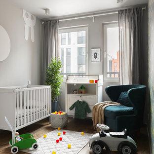 Ejemplo de habitación de bebé neutra actual, pequeña, con paredes grises y suelo de madera en tonos medios