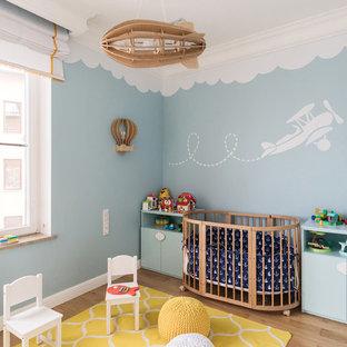 На фото: нейтральная комната для малыша в скандинавском стиле с синими стенами, паркетным полом среднего тона и коричневым полом