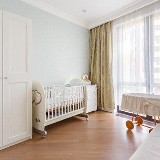 На фото: нейтральная комната для малыша в стиле современная классика с серыми стенами, паркетным полом среднего тона и коричневым полом с
