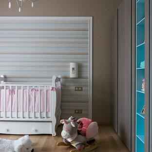 Cette image montre une chambre de bébé fille design avec un mur marron, un sol en bois brun et un sol marron.