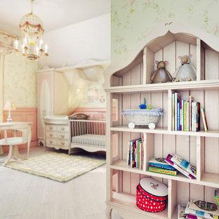 Foto di una cameretta per neonata mediterranea con pareti verdi e parquet chiaro