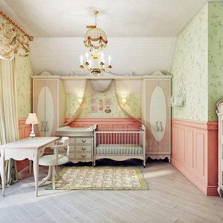 Ispirazione per una cameretta per neonata mediterranea con pareti verdi e parquet chiaro