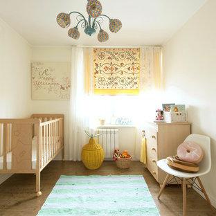 На фото: маленькая комната для малыша в скандинавском стиле с белыми стенами и паркетным полом среднего тона для девочки с