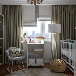 На фото: нейтральная комната для малыша в скандинавском стиле с серыми стенами, паркетным полом среднего тона и коричневым полом с
