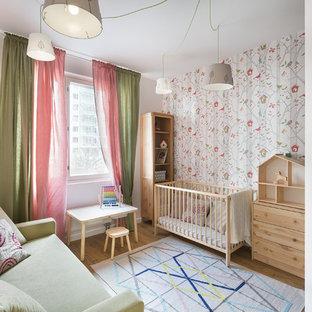 Modelo de habitación de bebé niña nórdica, pequeña, con paredes multicolor, suelo laminado y suelo beige