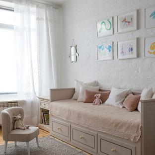 Imagen de habitación de bebé niña tradicional renovada con paredes blancas, suelo de madera en tonos medios y suelo marrón