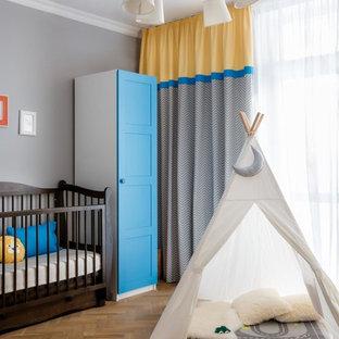 Пример оригинального дизайна интерьера: комната для малыша среднего размера в современном стиле с серыми стенами, паркетным полом среднего тона и коричневым полом для мальчика