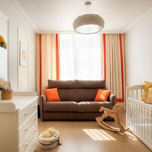 Diseño de habitación de bebé neutra tradicional renovada, de tamaño medio, con paredes blancas, suelo de corcho y suelo beige