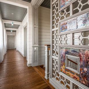 Стильный дизайн: большой коридор в стиле современная классика с белыми стенами, паркетным полом среднего тона и коричневым полом - последний тренд