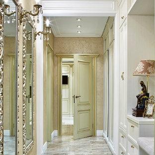 Inspiration pour un couloir traditionnel avec un mur beige, un sol en marbre et un sol beige.