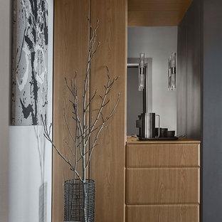 На фото: коридор в современном стиле с полом из керамогранита, белыми стенами и серым полом с