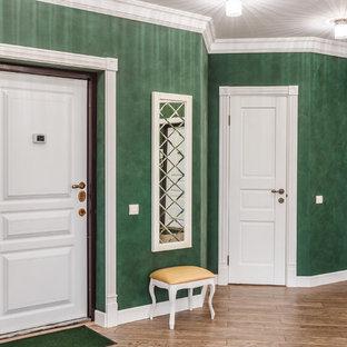 Exempel på en hall, med gröna väggar och laminatgolv
