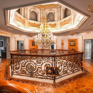 Пример оригинального дизайна: коридор в викторианском стиле с белыми стенами, паркетным полом среднего тона и коричневым полом