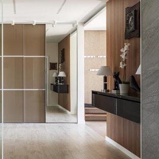 Foto på en stor funkis hall, med klinkergolv i porslin, beiget golv och bruna väggar