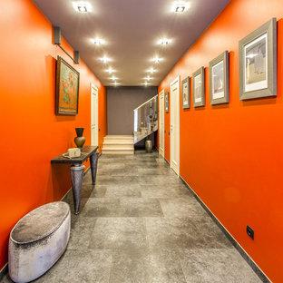 Idee per un grande ingresso o corridoio bohémian con pavimento in gres porcellanato e pareti arancioni