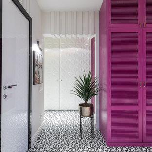 Modern inredning av en mellanstor hall, med vita väggar, klinkergolv i porslin och vitt golv