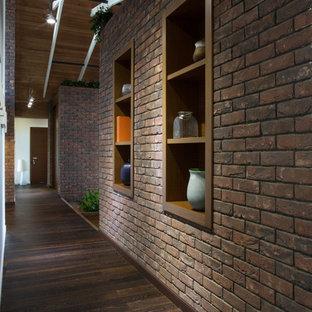 他の地域の大きいコンテンポラリースタイルのおしゃれな廊下 (茶色い壁、ラミネートの床、茶色い床) の写真