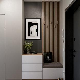 Bild på en mellanstor funkis hall, med grå väggar, laminatgolv och beiget golv